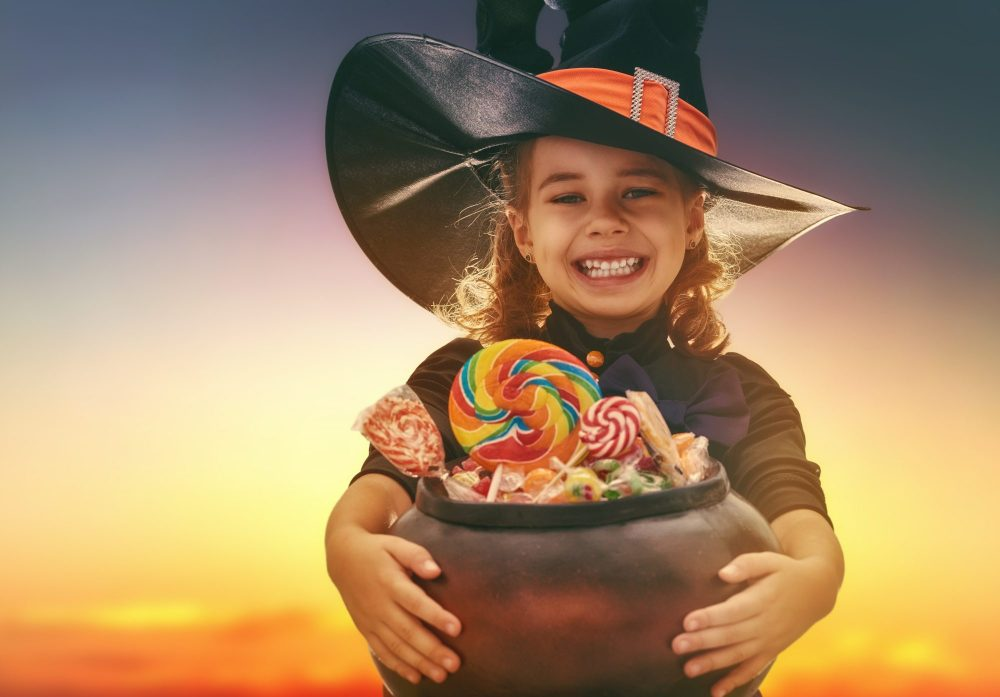 happy-halloween-cute-little-witch-with-candy-child-girl-outdoors